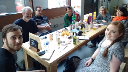 Members of ORG Birmingham at their first meet up sitting round a table with drinks and snacks.